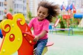 s úsměvem kudrnaté africké americké malé dítě na Houpací kůň na hřišti