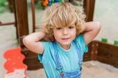 Selektivní fokus roztomilý chlapeček při pohledu kamery na hřišti