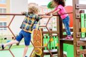 Zwei multiethnische kleine Kinder klettern und spielen auf Spielplatz