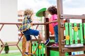 lockige multiethnischen kleine Kinder Klettern und Spaß am Spielplatz