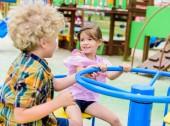 Fotografie Zwei entzückende kleine Kinder auf Karussell auf Spielplatz