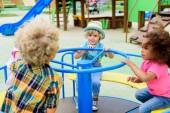 Fotografie fröhliche multiethnische Gruppe kleiner Kinder auf Karussell auf Spielplatz