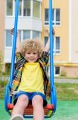 Fotografie glücklich lockiges kleiner Junge reitet auf Schaukel auf Spielplatz