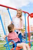 Fotografie selektiven Fokus des Lächelns Mutter Reiten Tochter auf Schaukel auf Spielplatz