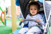 selective focus of african american toddler sitting in baby carriage at playgorund