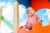 nízký úhel pohledu usmívající se malé dítě baví u hřiště