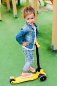 Fotografie selektiven Fokus lächelnden kleinen Kindes stehend mit Kick Scooter auf Spielplatz