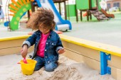 Fotografie curly african american little child playing with plastic scoop and bucket in sandbox at playground