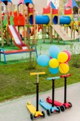 three childish kick scooters placed in row with colorful air balloons at playground