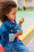 Fotografie side view of curly african american little child playing with soap bubbles