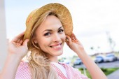 portrait of smiling young woman in straw hat on blurred background