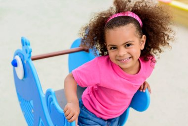 portrait of curly african american little child having at playground