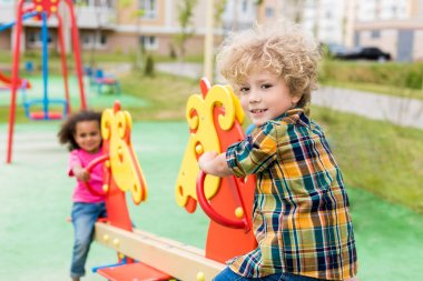 selective focus of little smiling boy riding on rocking horse with curly child at playground