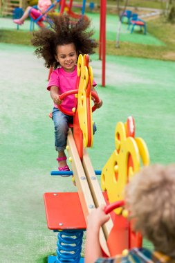 happy curly african american child riding on rocking horse with boy at playground