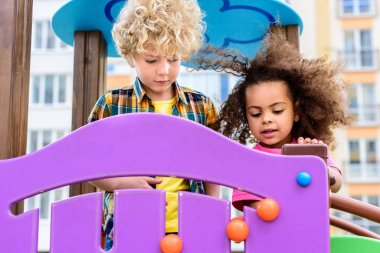 two curly multiethnic little kids having fun at playground