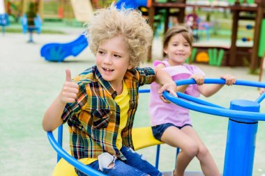 adorable curly boy doing thumb up gesture while riding on carousel with little child at playground