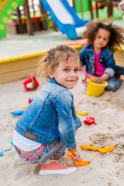 selective focus of smiling little child sitting in sandbox with plastic scoop while her friend sitting behind at playground