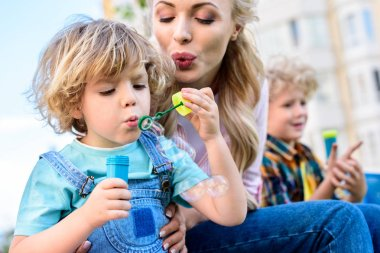 selective focus of mother and little son using bubble blower while other boy sitting near