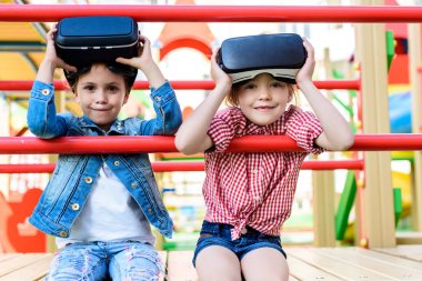 adorable little children taking off virtual reality headsets at playground