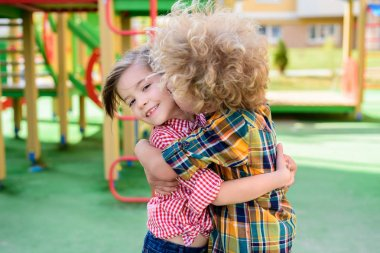 selective focus of curly boy kissing and hugging little sister at playground
