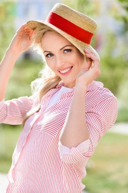 Portrait of smiling young woman in straw hat on blurred background stock vector