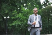 Fotografie bearded smiling businessman walking on street and holding disposable coffee cup