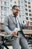 bearded businessman with disposable cup of coffee and smartphone leaning on bike