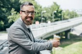 Fotografie handsome businessman holding disposable cup of coffee