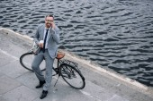 Fotografie businessman with coffee to go talking on smartphone and standing with bike on quay