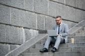 Fotografie vousatý podnikatel pomocí přenosného počítače a sedí na schodech s kávou jít