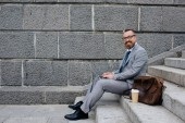 Fotografie businessman with bag and disposable cup of coffee using laptop and sitting on stairs