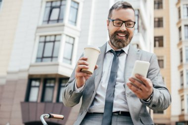 Bearded businessman using smartphone and holding paper cup of coffee stock vector