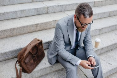 businessman using smartphone and sitting on stairs with leather bag and coffee
