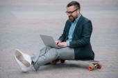 Stylový Evropský muž pomocí přenosného počítače a sedí na skateboardu v městě