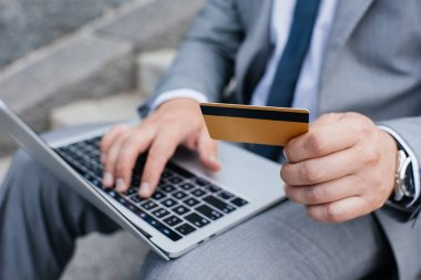 cropped view of man shopping online with laptop and credit card