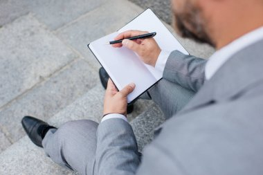 cropped view of businessman in grey jacket writing in diary