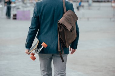 cropped back view of man with leather backpack and skateboard walking in city
