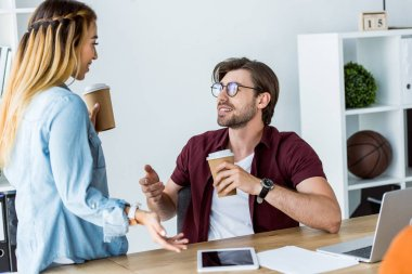 multicultural colleagues talking and holding disposable coffee cups in office