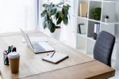 Fotografie laptop a kávu v pohárek na stole v pracovním prostoru obchodní