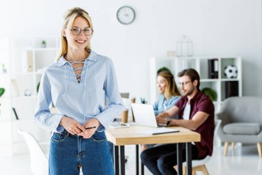 beautiful woman standing in office of startup project and looking at camera