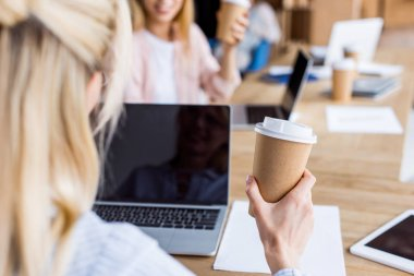 cropped image of colleagues working on startup project in office with coffee and gadgets