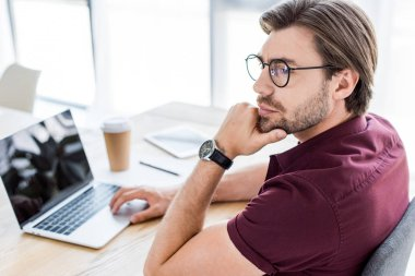 pensive handsome businessman working on startup project in office and looking away