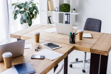 laptops, tablet and disposable coffee cups on tables in business office