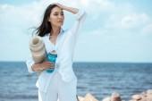 Asiatka mladá žena držící sportovní láhev vody a jóga mat po moři