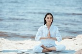 attractive asian woman meditating in anjali mudra (salutation seal) pose on yoga mat by sea