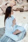 Nagy látószögű tekintettel összpontosított ázsiai nő meditál csukott szemmel Anjali mudrában jelent a jóga mat