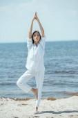 young woman standing in asana vrikshasana (tree pose) on beach by sea