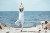 asian woman standing in asana vrikshasana (tree pose) on beach by sea