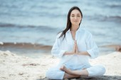 Fotografie attractive young asian woman in anjali mudra (salutation seal) pose on beach