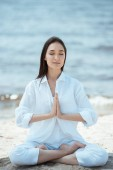 Fotografie young asian woman in anjali mudra (salutation seal) pose on beach